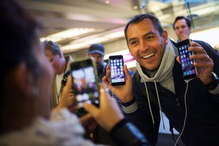 Michele Mattana of Sardinia, Italy, poses with an iPhone 6 Plus and an iPhone 6 on the first day of sales at the Fifth Avenue store in Manhattan, New York