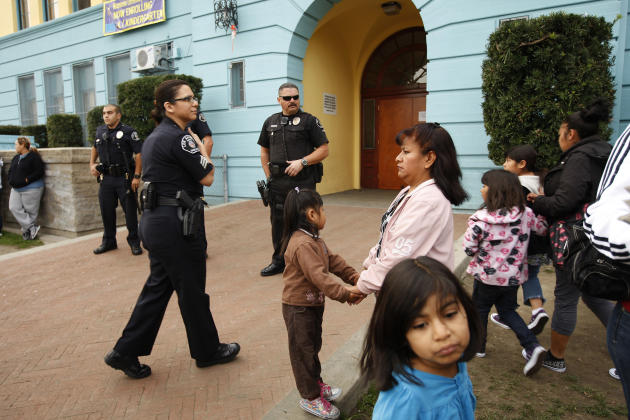 Los Angeles School Police officers provide security as parents and children gather outside of Miramonte Elementary school to protest as investigation continues into bizarre sexual abuse scandal in Los