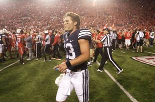 BYU QB Riley Nelson walks away from Utah fans who prematurely rushed the field with 1 second left. (AP)
