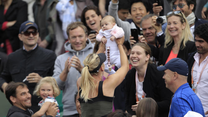 Maria Sharapova of Russia holds an unidentified baby after winning the women's final match against Sara Errani of Italy at the French Open tennis tournament in Roland Garros stadium in Paris, Saturday June 9, 2012. Sharapova won in two sets 6-3, 6-2. (AP Photo/Bernat Armangue)