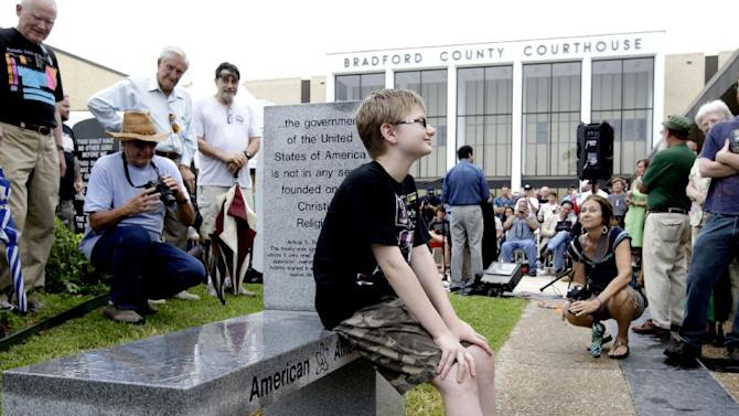 Chandler Allen, 10, is the first person to sit on the bench during the unveiling of an Atheist monument outside the Bradford County Courthouse on Saturday, June 29, 2013 in Stark, Fla. The New Jersey-based group American Atheists unveiled the 1,500-bound granite bench Saturday as a counter to the religious monument in what's called a free speech zone. Group leaders say they believe it's the first such atheist monument on government property. About 200 people attended the event.(AP Photo/The Gainesville Sun, Matt Stamey)