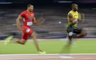 Jamaica's Usain Bolt leads USA's Ryan Bailey to win the gold medal in the en's 4x100-meter during the athletics in the Olympic Stadium at the 2012 Summer Olympics, London, Saturday, Aug. 11, 2012. (AP Photo/Matt Slocum)