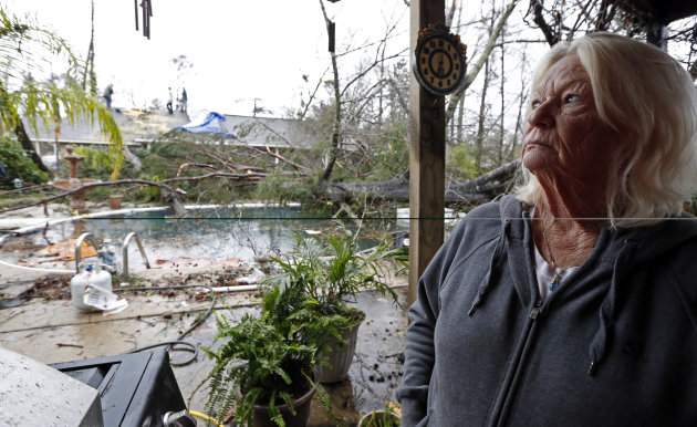 Dot Peek, looks at the damage Sunday&#39;s tornado caused her and her daughter&#39;s home next door in Hattiesburg, Miss., Monday, Feb. 11, 2013. The tornado damaged both her roof and that of her daughter&#39;s house. Peek said she recently had the swimming pool refinished and now she has two trees in the pool as result from the strong winds that caused damage throughout the South Mississippi college town. (AP Photo/Rogelio V. Solis)