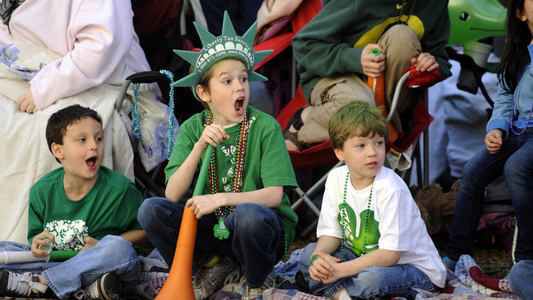 Jacob Tidwell, center, and his friends Donavan Mock, left, and Preston Vasquez react to a band during Savannah's 189-year-old St. Patrick's Day parade, Saturday, March 16, 2013, in Savannah, Ga. Started in 1824 by early Irish immigrants to Georgia, the parade has ballooned into a sprawling street party that makes for Savannah's most profitable tourism event. (AP Photo/Stephen Morton)