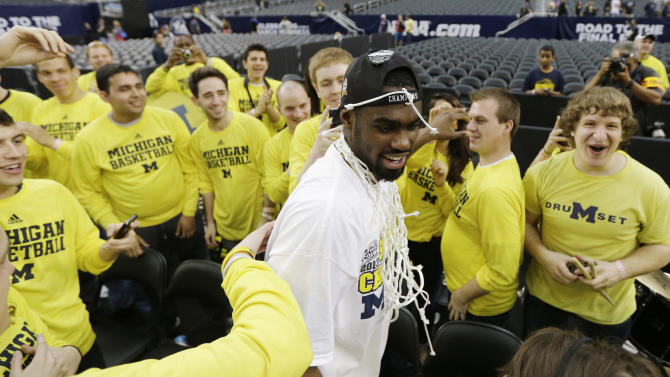 Michigan's Tim Hardaway Jr. celebrates with the band after a regional final game against Florida in the NCAA college basketball tournament, Sunday, March 31, 2013, in Arlington, Texas. Michigan won 79-59 to advance to the Final Four. (AP Photo/David J. Phillip)