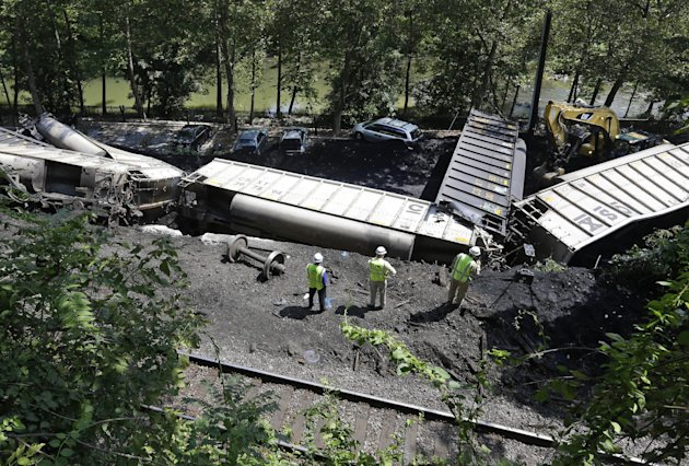 Officials inspect part of a CSX freight train that derailed alongside a parking lot overnight in Ellicott City, Md., Tuesday, Aug. 21, 2012. Authorities say the train, hauling coal from West Virginia 