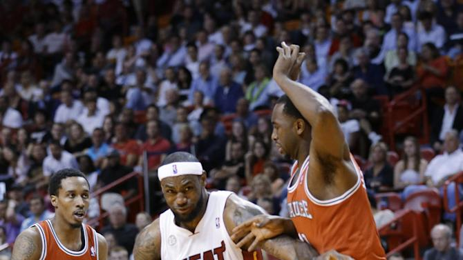 Miami Heat forward LeBron James (6) drives to the basket past Milwaukee Bucks guard Brandon Jennings, left, and forward Luc Richard Mbah a Moute, right, during the first half of an NBA basketball game, Tuesday, April 9, 2013, in Miami. (AP Photo/Wilfredo Lee)