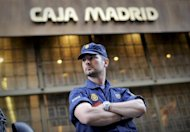 A policeman stands guard on May 14 outside Caja Madrid's headquarters in Madrid, which was bought by Bankia bank, during a protest