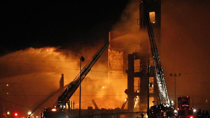 Firefighters battle a fire in a warehouse on York Street near Kensington Avenue in Philadelphia early Monday, April 9, 2012. Two firefighters died after a wall collapsed on them while they fought the massive early-morning blaze. (AP Photo/Joseph Kaczmarek)