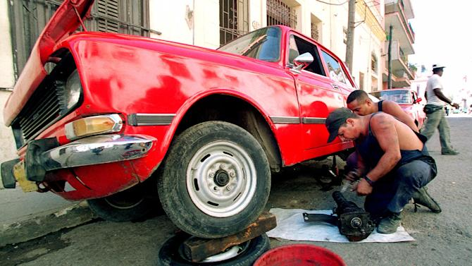 FILE - In this November 1999 file photo, mechanic William Escalante repairs an old Russian-made Moskvitch car in Havana's Centro Habana neighborhood. Ladas and Moskvitch cars are the two Soviet-era vehicles that are mainstays on Cuban roads. But parts can be expensive or hard to come by, so Miami-area auto parts dealer Fabian Zakharov is tapping into the niche market. (AP Photo/Jose Goitia, File)