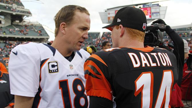 Denver Broncos quarterback Peyton Manning (18) talks with Cincinnati Bengals quarterback Andy Dalton (14) after the Broncos defeated the Bengals 31-23 in an NFL football game, Sunday, Nov. 4, 2012, in Cincinnati. (AP Photo/Tom Uhlman)
