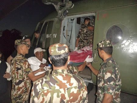 Handout photo of Nepalese army personnel carrying a victim rescued from the avalanche inside a helicopter at Thorang-La in Annapurna Region