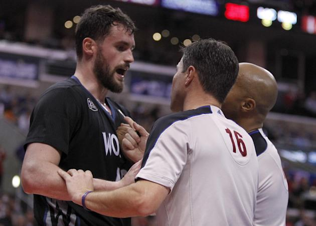 Referees David Guthrie (16) and Marc Davis, right, try to calm down Minnesota Timberwolves forward Kevin Love, left, after a physical foul by Los Angeles Clippers forward Matt Barnes in the second hal