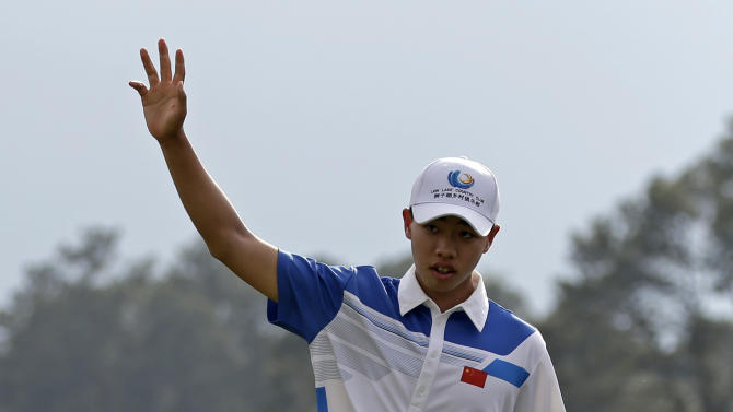 Amateur Guan Tianlang, of China, waves after a birdie putt on the 18th green during the first round of the Masters golf tournament Thursday, April 11, 2013, in Augusta, Ga. (AP Photo/Darron Cummings)