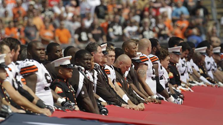 Cleveland Browns quarterback Colt McCoy, center, along with other members of the Browns, fire department and armed services hold a United States flag during the national anthem before an NFL football game against the Cincinnati Bengals, Sunday, Sept. 11, 2011, in Cleveland. (AP Photo/Tony Dejak)