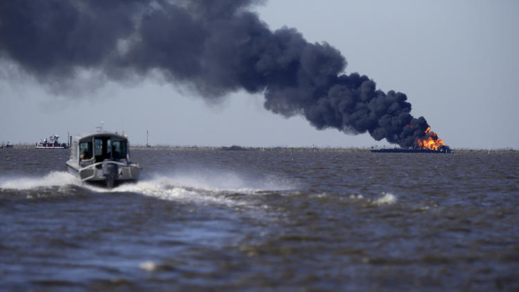 A fire still burns after a tugboat and barge hit a gas pipeline yesterday evening in Perot Bay in Lafourche Parish, La., Wednesday, March 13, 2013. (AP Photo/Gerald Herbert)