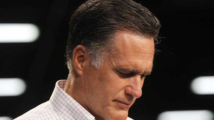 Republican presidential candidate, former Massachusetts Gov. Mitt Romney bows his head and leads a moment of silence for the Sikh shooting victims in Wisconsin before campaigning at Acme Industries in Elk Grove Village, Ill.,Tuesday, Aug. 7, 2012. (AP Photo/Charles Dharapak)