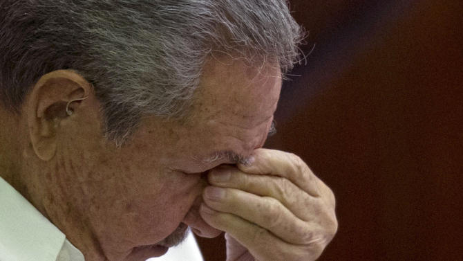 Cuba's President Raul Castro pauses to remove his glasses during his speech to lawmakers at the closing ceremony of the legislative session at the National Assembly in Havana, Cuba, Saturday, Dec. 20, 2014. While praising the historic agreement between Cuba and the U.S. to restore relations, Castro made it clear that the agreement only goes so far, reminding the audience of his call for the U.S. Congress to end the trade embargo. (AP Photo/Ramon Espinosa)