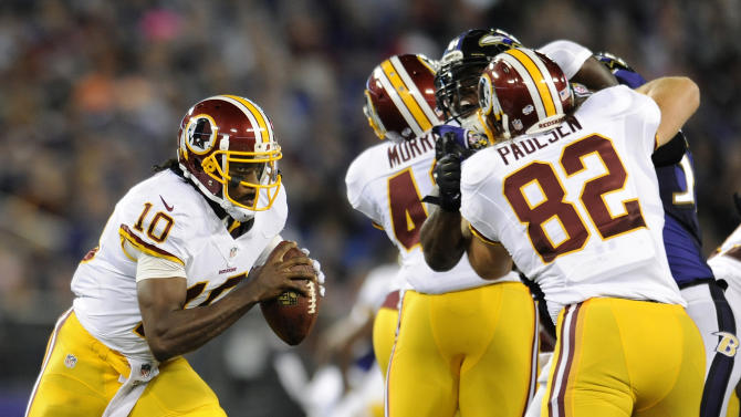 Washington Redskins quarterback Robert Griffin III, left, looks for a receiver as teammates hold back Baltimore Ravens defenders in the first half of an NFL preseason football game, Saturday, Aug. 23, 2014, in Baltimore. (AP Photo/Gail Burton)