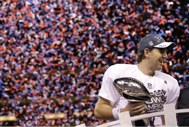 New York Giants quarterback Eli Manning holds up the Vince Lombardi Trophy while celebrating his team's 21-17 win over the New England Patriots in the NFL Super Bowl XLVI football game, Sunday, Feb. 5