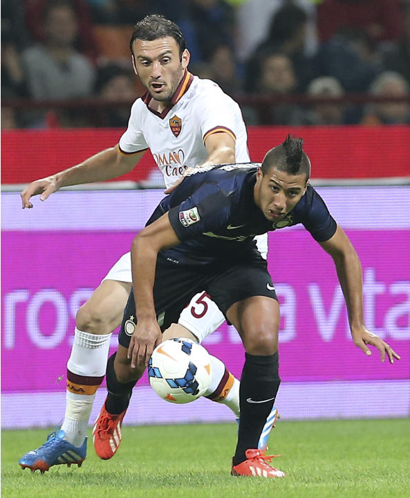 Inter Milan midfielder Saphir Taider, foreground, of Algeria, challenges for the ball with AS Roma defender Vasilis Torosidis, of Greece, during the Serie A soccer match between Inter Milan and Roma a