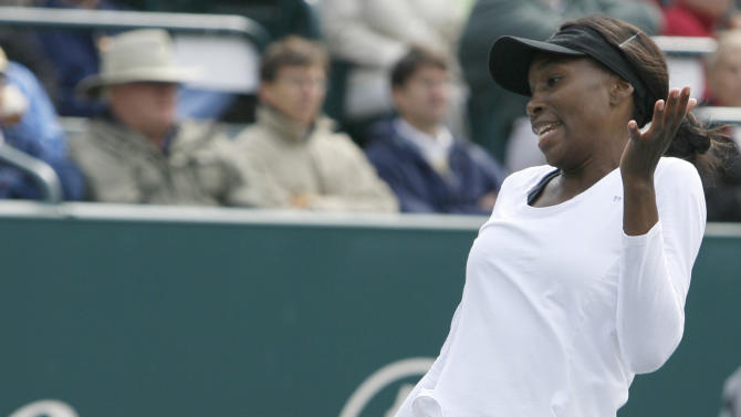Venus Williams reacts to a bad shot against Samantha Stosur, of Australia, during their quarterfinals match at the Family Circle Cup tennis tournament in Charleston, S.C., Friday, April 6, 2012.  (AP Photo/Mic Smith)