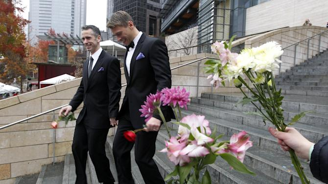 Dan Savage, left, and his husband Terry Miller walk past well-wishers after wedding at Seattle City Hall, becoming among the first gay couples to legally marry in the state, Sunday, Dec. 9, 2012, in Seattle. Gov. Chris Gregoire signed a voter-approved law legalizing gay marriage Dec. 5 and weddings for gay and lesbian couples began in Washington state on Sunday, following the three-day waiting period after marriage licenses were issued earlier in the week. (AP Photo/Elaine Thompson)