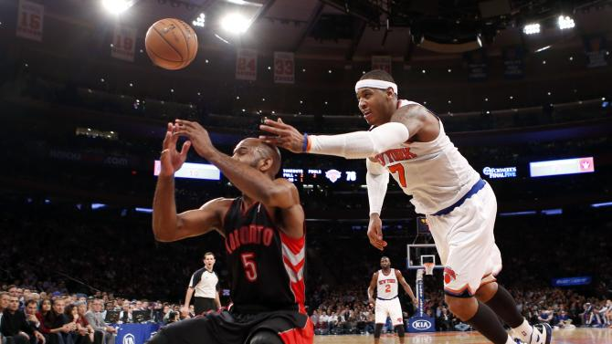 New York Knicks' Carmelo Anthony dives to try to save a ball over Toronto Raptors' John Lucas lll during the fourth quarter in their NBA basketball game in New York