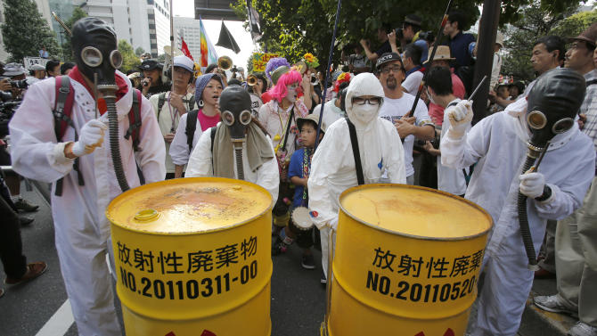 Anti-nuclear protesters, wearing gas-masks, beat metal drums as they march near the Japan's parliament complex in Tokyo, Sunday, July 29, 2012. Thousands of the protesters rallied to demand the government abandon nuclear power after the accident last year in northern Fukushima. The word on yellow drums reads: Nuclear waste. (AP Photo/Shizuo Kambayashi)