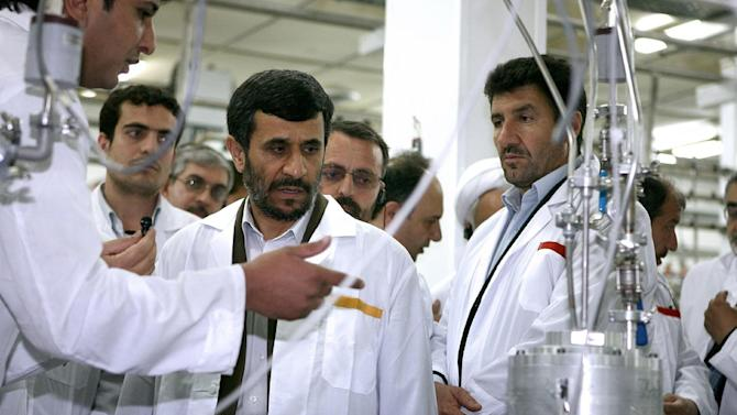 FILE- In this April 8, 2008, file photo  released by the Iranian President's Office, Iranian President Mahmoud Ahmadinejad, center, listens to a technician during his visit of the  Natanz Uranium Enrichment Facility some 200 miles (322 kilometers) south of the capital Tehran, Iran. For the first time in nearly two decades of escalating tensions over the Iranian nuclear program, it appears that world leaders are genuinely concerned that an Israeli military attack on the Islamic Republic could be imminent, an action that many fear might trigger war, terrorism and global economic havoc. (AP Photo/Iranian Presidents office, File)