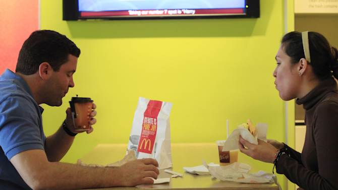 """Carlos Gonzalez and Elsa Guzman eat breakfast at a McDonald's restaurant, Wednesday, Sept. 12, 2012 in New York. McDonald's restaurants across the country will soon get a new menu addition: The number of calories in the chain's burgers and fries. The world's biggest hamburger chain said Wednesday that it will post calorie information on restaurant and drive-thru menus nationwide starting Monday. The move comes ahead of a regulation that could require major chains to post the information as early as next year. """"It's good to know the calories I'm consuming so I can plan out my whole day,"""" said Gonzalez. (AP Photo/Mark Lennihan)"""