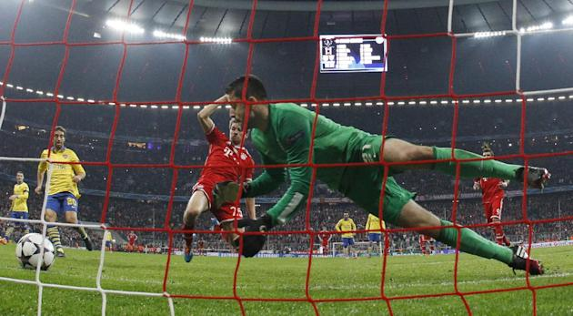 Arsenal's goalkeeper Lukasz Fabianski, right, jumps for the ball after saving a shot from the penalty spot by Bayern's Thomas Mueller during the Champions League round of 16 second leg soccer