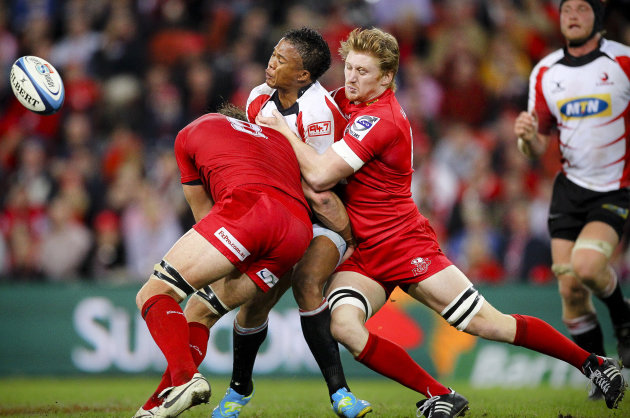 Queensland Reds players Scott Higginbotham (L) and Eddie Quirk (R) tackle Golden Lions flyhalf Elton Jantjies (C) during their Super 15 rugby union match at Suncorp Stadium in Brisbane on May 19, 2012