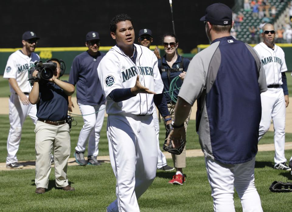 Seattle Mariners pitcher Felix Hernandez walks to shake hands with manager Eric Wedge after Hernandez pitched a perfect game against the Tampa Bay Rays, Wednesday, Aug. 15, 2012, in Seattle. The Mariners defeated the Rays 1-0 in the baseball game. (AP Photo/Ted S. Warren)