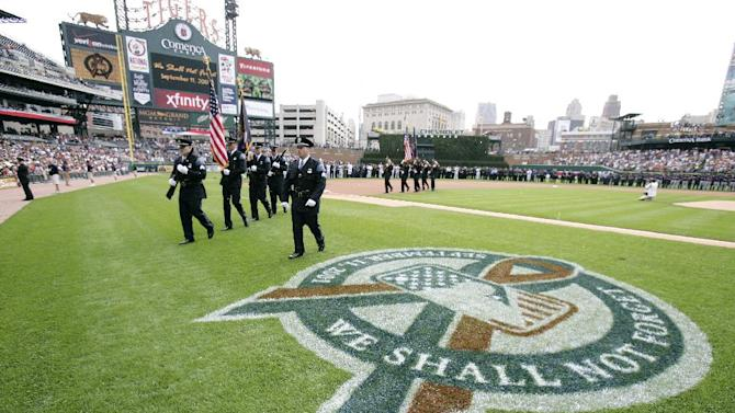 Members of the Farmington Hills Police Honor Guard march past the Major League Baseball official logo commemorating the Sept. 11 tragedy during a ceremony at Comerica Park, Sunday, Sept. 11, 2011, in Detroit. The Detroit Tigers take on the Minnesota Twins in a baseball game Sunday. (AP Photo/Duane Burleson)