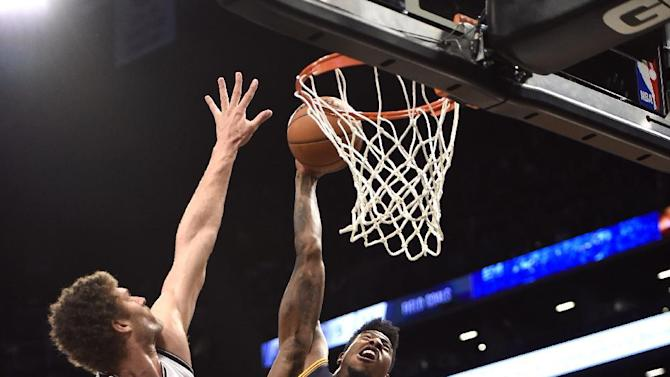 Cleveland Cavaliers guard Iman Shumpert (4) dunks over Brooklyn Nets center Brook Lopez (11) in the first half of an NBA basketball game on Friday, March 27, 2015, in New York. (AP Photo/Kathy Kmonicek)