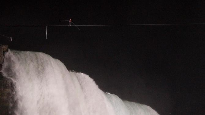 Nik Wallenda walks across Niagara Falls on a tightrope as seen from Niagara Falls, N.Y., Friday, June 15, 2012. Wallenda has finished his attempt to become the first person to walk on a tightrope 1,800 feet across the mist-fogged brink of roaring Niagara Falls. The seventh-generation member of the famed Flying Wallendas had long dreamed of pulling off the stunt, never before attempted. (AP Photo/James P. McCoy)