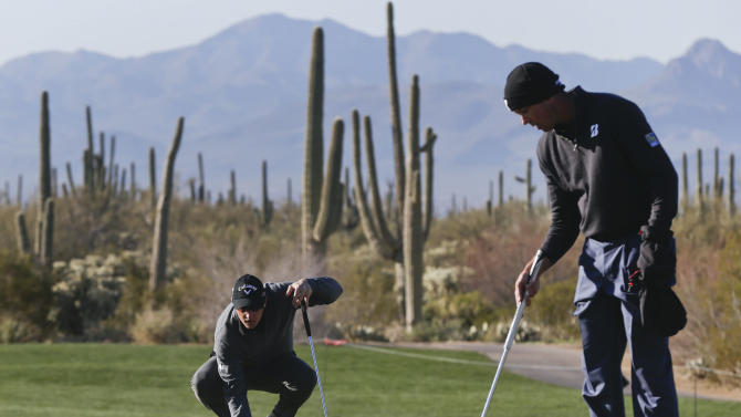 Belgium's Nicolas Colsaerts, left, places his ball on the fourth green as Matt Kuchar lines up his putt during a third round match at the Match Play Championship golf tournament, Saturday, Feb. 23, 2013, in Marana, Ariz. (AP Photo/Julie Jacobson)