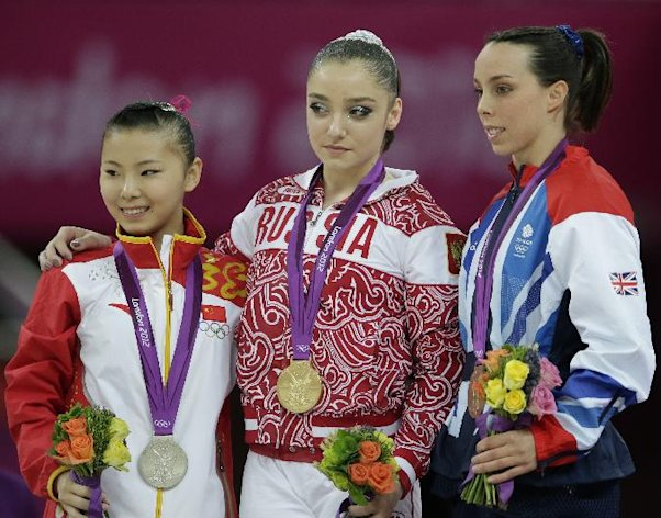 Russian gold medallist gymnast Aliya Mustafina, center, Chinese silver medallist He Kexin, left, and Britain's bronze medallist Elizabeth Tweddle stand during the podium ceremony for the uneven bars during the artistic gymnastics women's apparatus finals at the 2012 Summer Olympics, Monday, Aug. 6, 2012, in London. (AP Photo/Gregory Bull)