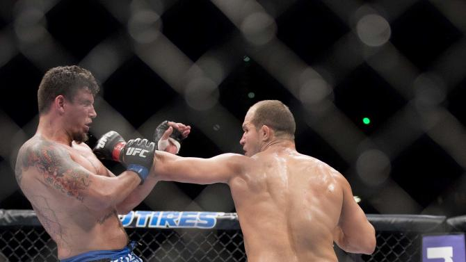 Junior Dos Santos, right, lands a punch against Frank Mir sending him to the mat in the second round during a UFC 146 heavyweight bout, Saturday, May 26, 2012, in Las Vegas. Dos Santos won by knockout in the second round. (AP Photo/Julie Jacobson)