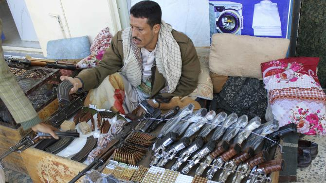A man holds a rifle magazine as he sits at his stall on a street in Saada