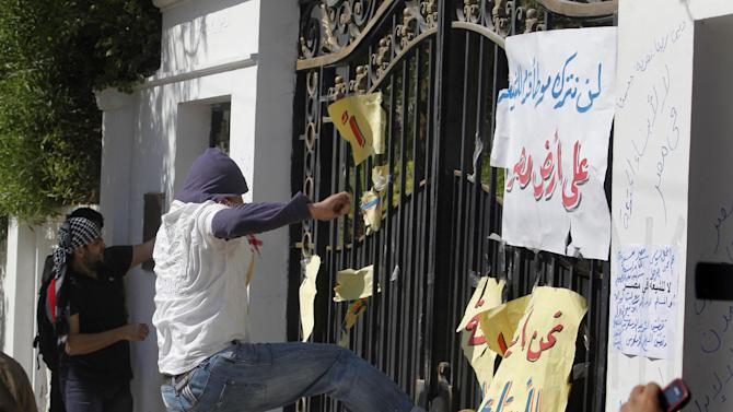 "Egyptian protesters try to destroy the gate at the residence of Iran's top diplomat in Cairo, Egypt, Friday, April 5, 2013. The protest was sparked after Iranian tourists arrived in Egypt this week on the first commercial flights between the two countries in 30 years. Arabic reads,""we will not let Shiites step in Egypt."" (AP Photo/Amr Nabil)"