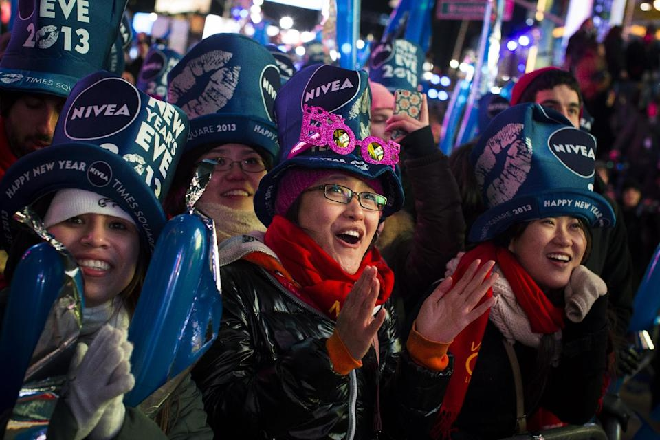 Qi Zhao, 25, of China, center, joins others in Times Square at the New Year's Eve celebration, Monday, Dec. 31, 2012, in New York. (AP Photo/John Minchillo)