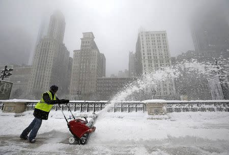 A worker pushes a snow plough to clear a path during blizzard conditions in Chicago