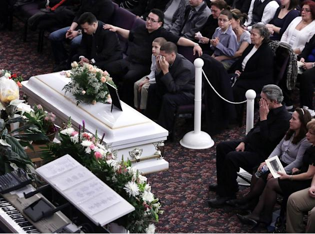 Steven Sierra, husband of Sarai Sierra, upper center, and Dennis Jimenez, right, wipe their eyes during her funeral, at the Christian Pentecostal Church, in the Staten Island borough of New York,  Fri