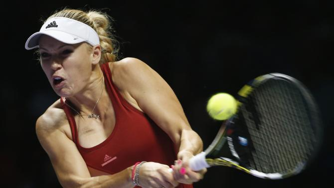 Caroline Wozniacki of Denmark hits a return to Serena Williams of the U.S. during their WTA Finals singles semi-finals tennis match at the Singapore Indoor Stadium