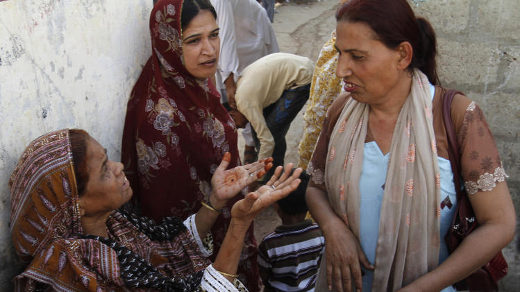 In this picture taken on Monday, April 15, 2013, Bindiya Rana, right, a transgender candidate in Pakistan's elections, talks with locals in Karachi, Pakistan. When Rana went door to door in the Karachi slum she hopes to represent, few people seemed to care about which gender she identifies with. They were more interested in what she was going to do to combat the street crime and electricity outages in their neighborhood if elected.(AP Photo/Shakil Adil)