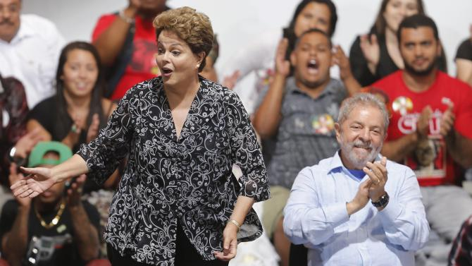 Brazil's President and Workers' Party presidential candidate Rousseff reacts next to Brazil's former President Lula da Silva as they attend a campaign rally in Sao Paulo