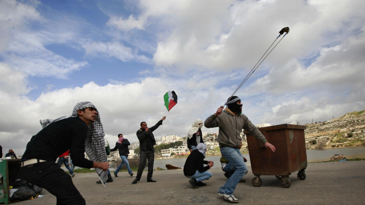 Palestinians throw rocks during clashes with Israeli troops, outside Ofer, an Israeli military prison near the West Bank city of Ramallah, Friday, Feb. 15, 2013. Palestinian demonstrators clashed with Israeli soldiers on Friday at a rally held in support of a prisoner observing an intermittent hunger strike to protest his incarceration. The Israeli military said about 200 Palestinians threw rocks at soldiers who responded with tear gas during the rally outside Ofer prison in the West Bank. The protesters called for the release of Samer Issawi, who has been on an on-again, off-again hunger strike for several months as he serves time for alleged terror activity. (AP Photo/Majdi Mohammed)