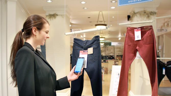 In this undated photo provided by Hointer, a woman demonstrates the Seattle store's shopping technology. Hointer displays clothing not in piles or on racks but as one piece hanging at a time, like a gallery. Shoppers just touch their smartphones to a coded tag on the item and then select a color and size via their phone. Technology in the store keeps track of the items, and by the time a shopper is ready to try them on, they're already at the dressing room. (AP Photo/Hointer)